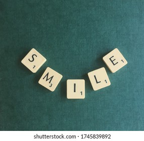 England, UK - 31st May 2020: The word smile, laid out in Scrabble game tiles in the shape of a smile, on the dark green reverse of a Scrabble board