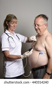 ENGLAND UK - CIRCA JUNE 2016 - Member of a hospital cardiac measurement team installing a ambulatory ECG monitor to an overweight male patient