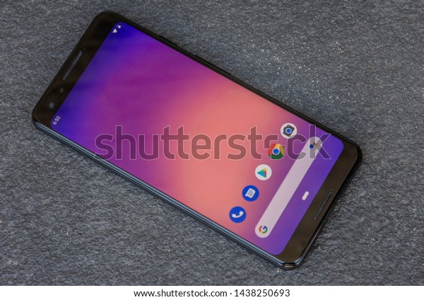 England, United Kingdom - June 30th 2019: The front screen of a Google Pixel 3 released by google an alphabet company in 2019. Image shows the latest cellphone on a gray stone background.