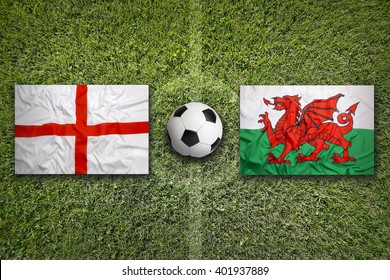 England vs. Wales flags on green soccer field