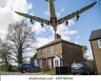 England/London March 12th 2019 Planes landing at London Heathrow Airport. An Emirates plane flies directly over residential housing as it approaches Heathrow's Southern runway (27L) before landing.