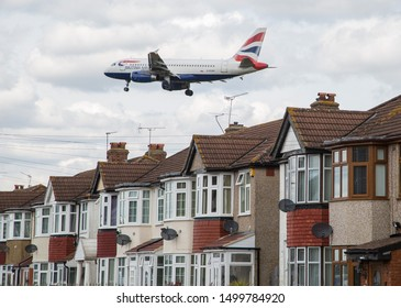 England/London March 12th 2019 Planes landing at London Heathrow Airport. A British Airways Airbus A319 plane flies over residential houses as it approaches Southern runway before landing