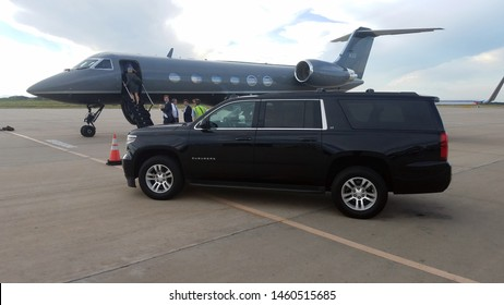 ENGLEWOOD, COLORADO - JULY 23, 2019: A black Chevrolet Suburban parked by a private jet