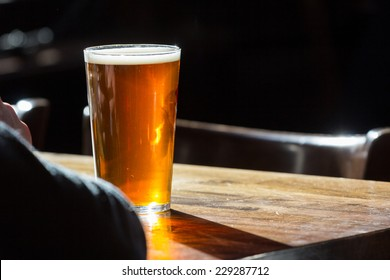 An english ale in front of an individual on a wooden table in a pub in London, UK