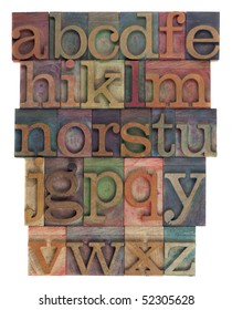 English alphabet (lower case) in vintage wooden letterpress type, stained by  inks of different colors, flipped horizontally, isolated on white