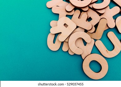 English alphabet made of natural yellow wood randomly scattered on a blue background. Latin letters.
