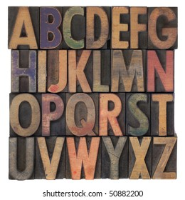English alphabet (upper case) in vintage wooden letterpress type, stained by different color ink, flipped horizontally, isolated on white