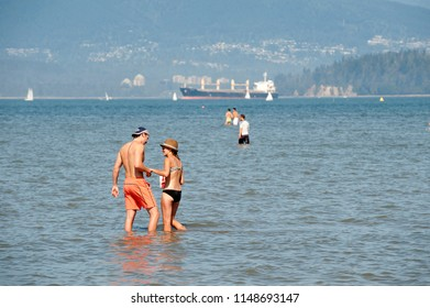 ENGLISH BAY - AUGUST 15, 2010: Sunbathers in the Kitsilano  and Spanish Beaches by Vancouver enjoy hot summer days in the waters of English Bay. British Columbia, Canada
