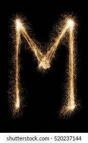 English big Letter M made from burning sparkles on black background. Shiny festive party firework font, latin alphabet text sign.