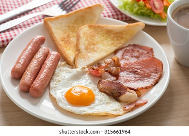 English breakfast with coffee on wood table.
