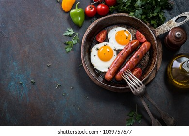 English breakfast in cooking pan with fried eggs, sausages, bacon and beans on dark stone background