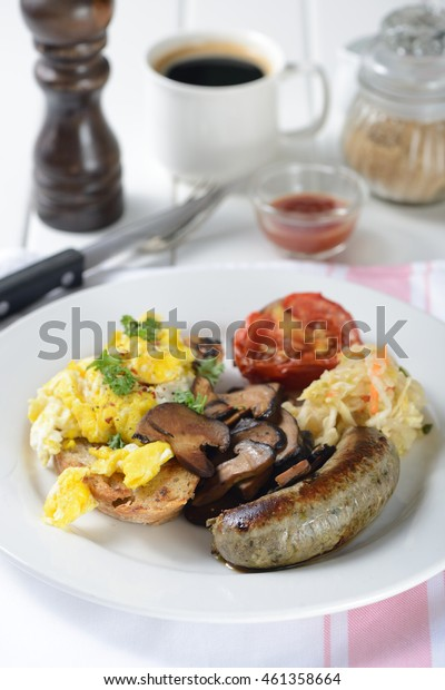 English breakfast with egg, sausage, vegetable, mushrooms, bread and tomato.
