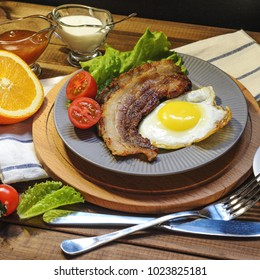 English Breakfast: fried egg with bacon, orange juice, tomatoes, zernovoi bread, lettuce leaf, top view.
