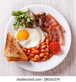 English breakfast: fried egg, bacon, beans and toast on a plate close-up. horizontal view from above