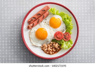 English breakfast with fried egg, beans, tomatoes, sausage, fresh lettuce leaf. Top view.
