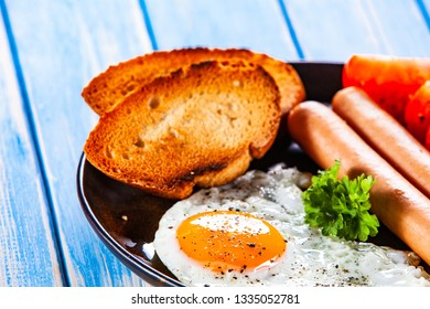 English breakfast - fried egg, sausages, toasts and vegetables