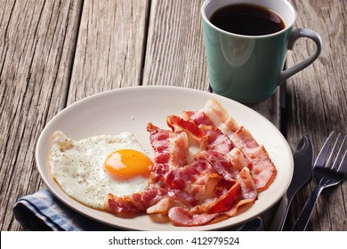 English breakfast with fried eggs and bacon, cup of coffee