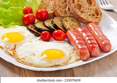 English breakfast - fried eggs, sausages, eggplant and tomatoes