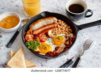 English breakfast in iron cooking pan with fried eggs, sausages, bacon, beaked beans, toasts, orange juice and black coffee on stone background.