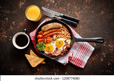 English breakfast in iron cooking pan with fried eggs, sausages, bacon, beaked beans, toasts, orange juice and black coffee on dark rusty background.