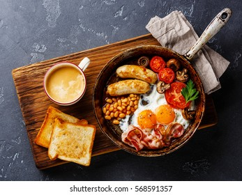English breakfast in pan with fried eggs, sausages, bacon, beans, toasts and coffee on dark stone background