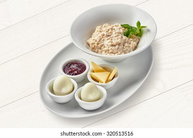 English breakfast with porridge and hard-boiled eggs on white background
