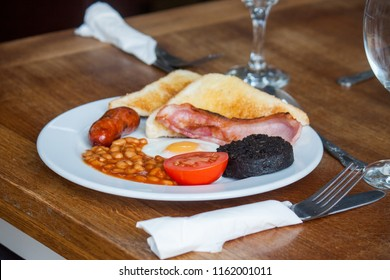 English Breakfast with sausage, egg, bacon, beans, black pudding and tomato.