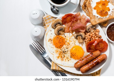 English breakfast of scrambled eggs with bacon, sausages and vegetables, top view, horizontal