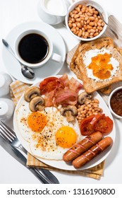 English breakfast of scrambled eggs with bacon, sausages and vegetables on white table, top view