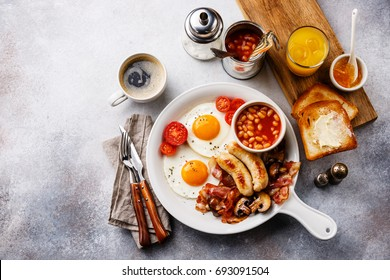 English breakfast in white pan with fried eggs, sausages, bacon, beans, toasts, orange fresh and coffee on white background copy space