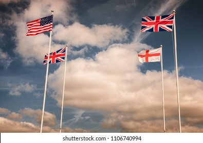 English, British and American flags on flagpoles with blue skies on a sunny day
