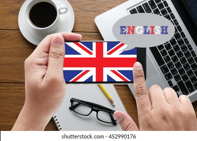 ENGLISH ( British England Language Education ) message on hand holding to touch a phone, top view, table computer coffee and book