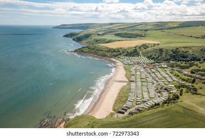 English caravan park and countryside. Aerial drone image looking over the English coastline and countryside down onto a sandy beach and static caravan site tucked into small valley.