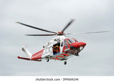 ENGLISH CHANNEL, NEAR BRIGHTON, ENGLAND - 19 MARCH 2016. A Coastguard Helicopter performs a rescue exercise in conjunction with a construction vessel.