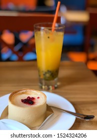 English cheesecake decorated with berries and lemonade with passion fruit on a table in a cafe. Photos of desserts, sweets, cheesecakes.