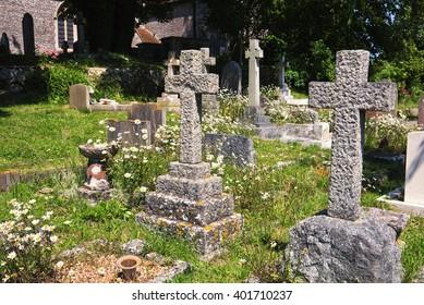 English church graveyard; verdant church yard with church and trees in background