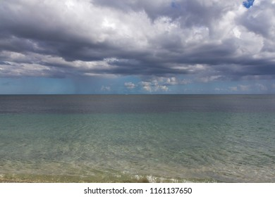 English coast looking out to a turquoise summer sea and heavy clouds