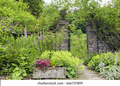 English cottage garden with stone wall rose arch gate, and colourful summer flowers in bloom .