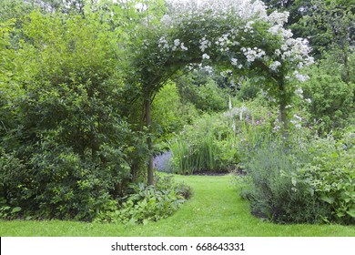 English cottage garden with white rose arch entrance, and colorful summer flowers in bloom .