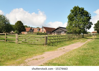 An English Country farm with a track and five bar gate and fence surrounding it