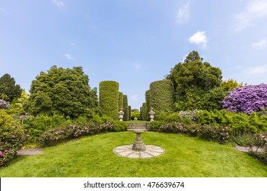 English country garden with sundial and topiary shrubs.