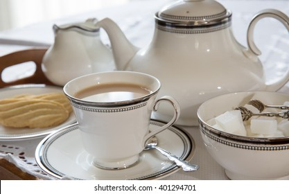 English cup of tea with teapot, sugar and biscuits