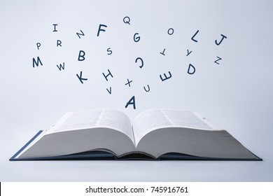 English dictionary with letters flying out of it on a white background.