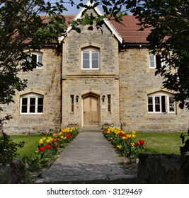 An English Farmhouse viewed from a Tulip bordered pathway