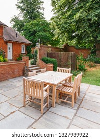 English garden and patio with wooden furniture outside a Victorian house in Buckinghamshire, UK