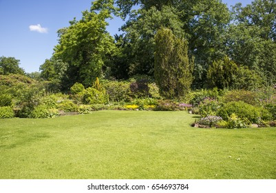 english garden with plants and flowers around green field of grass