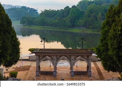 The English garden at Putrajaya Malaysia in the morning sunrise. Golden hour over the Putrajaya Lake. A Park in the government city outside of Kuala Lumpur. A traditional gate on the shore of the lake
