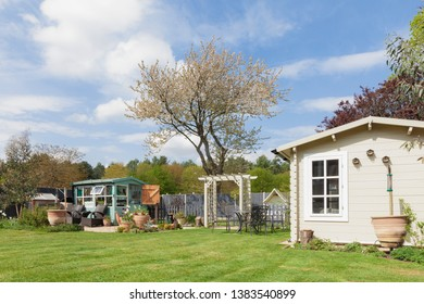 English garden in rural East Anglia in Norfolk. Large outside private garden with trees potting shed and summerhouse. Grass lawn and flower beds in spring time.