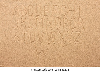 English, German, Portuguese alphabet  written on the sand, as background