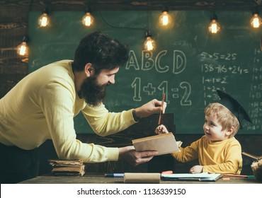 English grammar lesson. Little boy learn english grammar in classroom. Father teach english grammar to son. English grammar books.